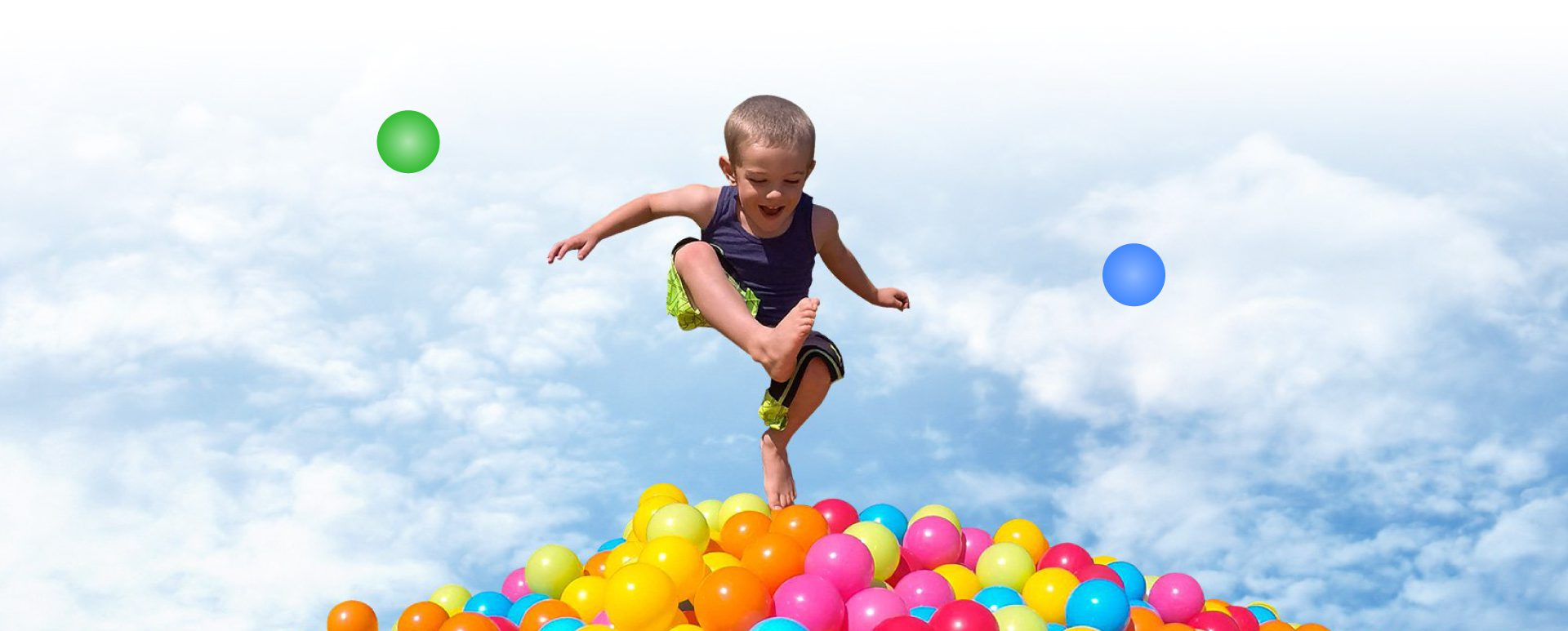 little boy jumping into a ball pit