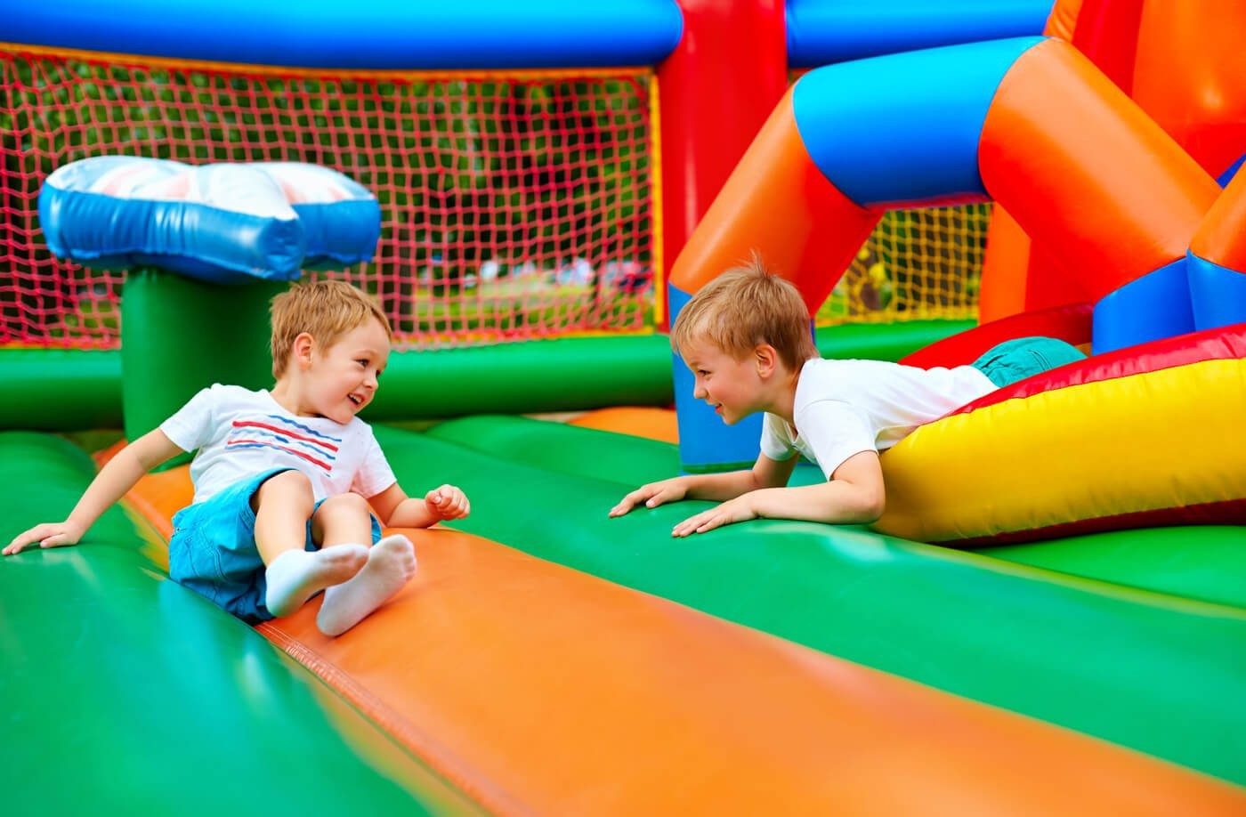 two little boys smiling in a bounce house