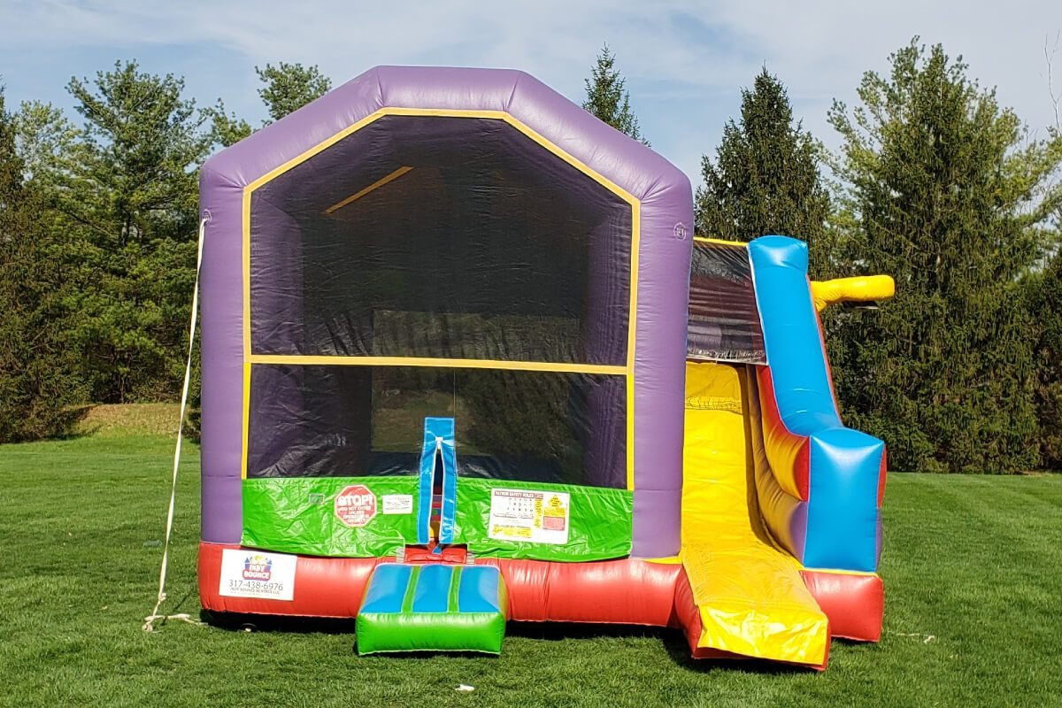 colorful bounce house with slide set up in indianapolis park
