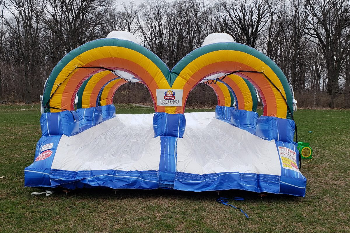 rainbow slip n slide bounce house set up in indianapolis park